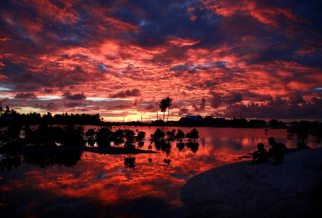 FILE PHOTO: Villagers watch the sunset over a small lagoon near the village of Tangintebu on South Tarawa in the central Pacific island nation of Kiribati May 25, 2013.  REUTERS/David Gray/