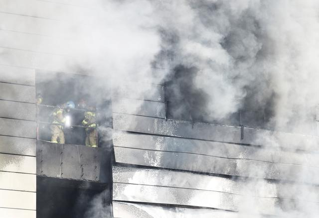 Firefighters search for survivors as smoke rises from a warehouse which is currently under construction, after it caught fire, in Icheon, South Korea, April 29, 2020.   Yonhap via REUTERS
