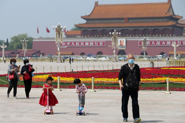 People wearing face masks following the coronavirus disease (COVID-19) outbreak walk past flower installations set up to mark the upcoming Labour Day holiday, at Tiananmen Square in Beijing, China April 29, 2020. China Daily via REUTERS