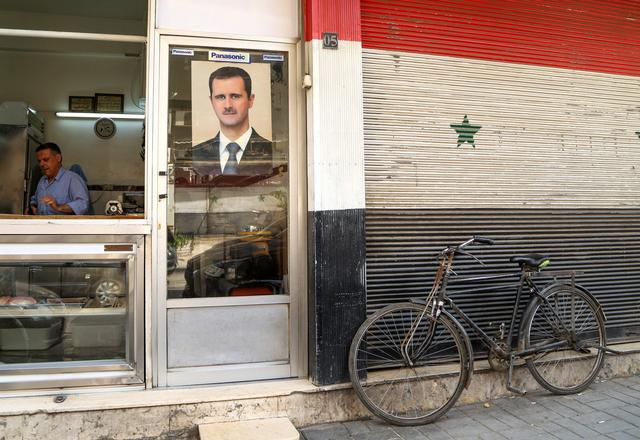 FILE PHOTO: A picture of Syrian President Bashar al-Assad is seen on a door of a butcher shop, during a lockdown to prevent the spread of the coronavirus disease (COVID-19), in Damascus, Syria April 22, 2020. REUTERS/Yamam Al Shaar