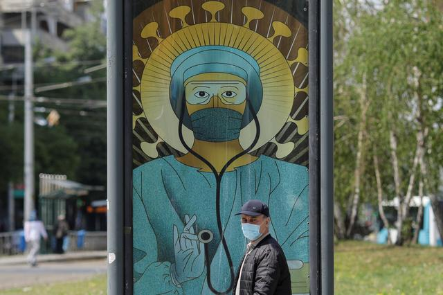 "A man passes by an outdoor poster that shows a medic depicted in a similar manner as Jesus Christ would be portrayed by Christian Orthodox religious paintings, in Bucharest, Romania, April 29, 2020. The poster, created by Romanian illustrator Wanda Hutira, is part of a ""Thank you doctors"" campaign. Inquam Photos/Octav Ganea via REUTERS"
