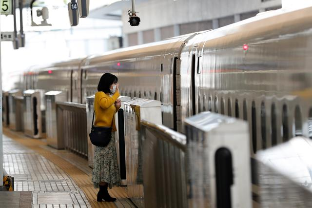 A woman waves to a relative aboard a train on a platform of Tokyo station where fewer people than usual are seen during Golden Week holidays following the coronavirus disease (COVID-19) outbreak, in Tokyo, Japan, April 29, 2020.REUTERS/Kim Kyung-Hoon