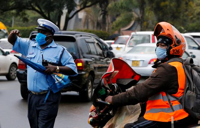 FILE PHOTO: A police officer directs motorists and riders before a curfew as a measure to contain the spread of the coronavirus disease (COVID-19), in downtown Nairobi, Kenya April 27, 2020. REUTERS/Thomas Mukoya