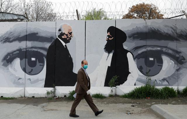 FILE PHOTO: An Afghan man wearing a protective face mask walks past a wall painted with photo of Zalmay Khalilzad, U.S. envoy for peace in Afghanistan, and Mullah Abdul Ghani Baradar, the leader of the Taliban delegation, in Kabul, Afghanistan April 13, 2020.REUTERS/Mohammad Ismail