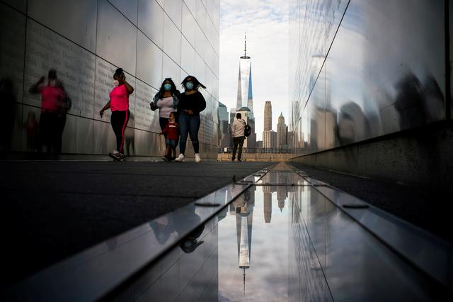 FILE PHOTO: People visit the Empty Sky Memorial as the The One World Trade Center in New York is seen from Liberty State Park after many New Jersey Parks set to re-open during the outbreak of the coronavirus disease (COVID-19) in Jersey City, New Jersey, U.S., May 2, 2020. REUTERS/Eduardo Munoz