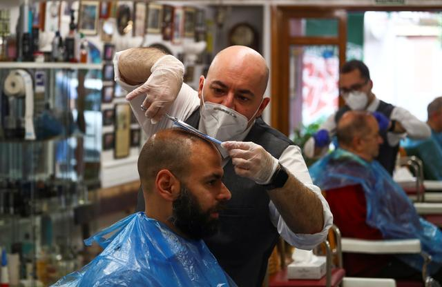 FILE PHOTO: A hairdresser wearing a protective mask and gloves cuts the hair of a customer at Madrid's oldest barber's shop, on the first day of opening during the lockdown, amid the coronavirus disease (COVID-19) outbreak in Madrid, Spain, May 4, 2020. REUTERS/Sergio Perez