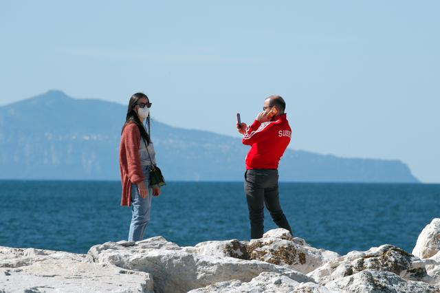People are seen at the seaside, as Italy begins a staged end to a nationwide lockdown due to the spread of the coronavirus disease (COVID-19), in Naples, Italy May 4, 2020. REUTERS/Ciro De Luca