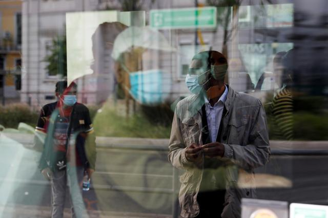 A man waiting at a bus stop is reflected in a bus window, as the country eases the lockdown due to the spread of the coronavirus disease (COVID-19), at Cais do Sodre station in Lisbon, Portugal May 4, 2020. REUTERS/Rafael Marchante