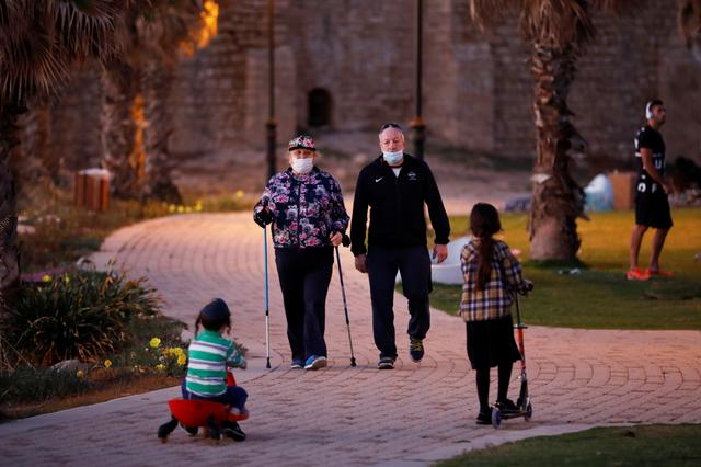 People wear face masks while exercising and kids play around near the shore of the Mediterranean Sea as the coronavirus disease (COVID-19) restrictions have eased in Ashkelon, Israel May 4, 2020. REUTERS/Amir Cohen