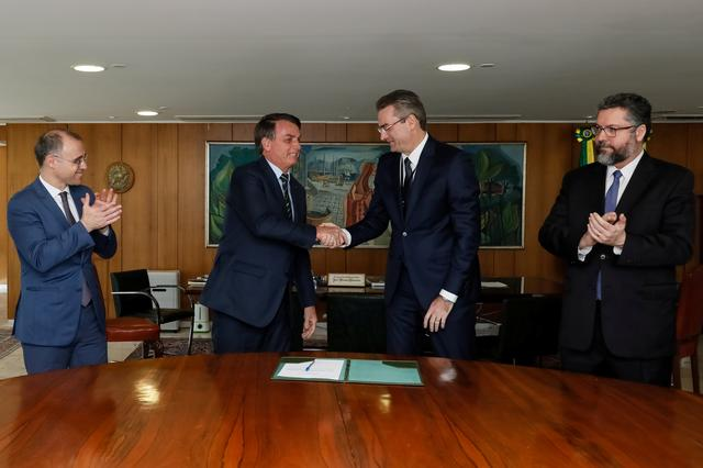 Brazil's President Jair Bolsonaro shakes hands with the new head of the federal police Rolando Alexandre de Souza as Justice Minister Andre Luiz de Almeida Mendonca and Foreign Minister Ernesto Araujo applaud at the Planalto Palace in Brasilia, Brazil, May 4, 2020. Isac Nobrega/Brazilian Presidency/Handout via REUTERS