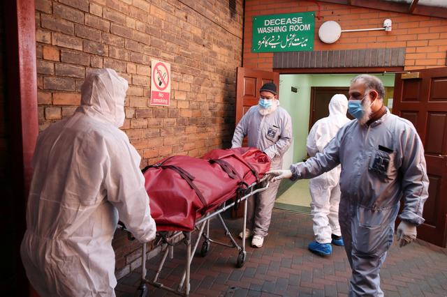 FILE PHOTO: Workers wearing protective equipment transport a body on the grounds of the Central Jamia Mosque Ghamkol Sharif, where a temporary morgue was set up as the coronavirus continues to spread in Birmingham, Britain, April 21, 2020. REUTERS/Carl Recine