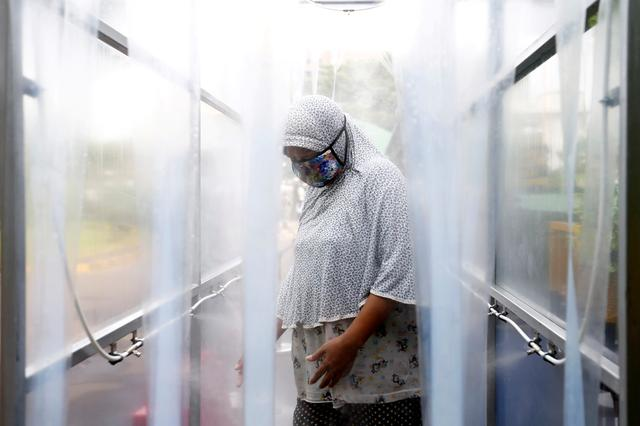 A woman wearing a protective face mask stands in a disinfection chamber before receiving rice from an automated rice ATM distributor amid the spread of the coronavirus disease (COVID-19) in Jakarta, Indonesia May 4, 2020. REUTERS/Ajeng Dinar Ulfiana