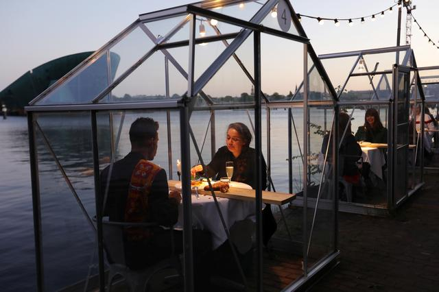"Models and family members are seen dining at a restaurant where they test waiters serving drinks and food to models pretending to be clients in a safe ""quarantine greenhouses"" in which guests can dine in Amsterdam, Netherlands May 5, 2020. REUTERS/Eva Plevier"