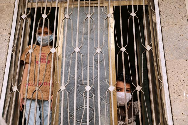 Children wearing protective masks look from behind a window during a 24-hour curfew amid concerns about the spread of the coronavirus disease (COVID-19), in Sanaa, Yemen May 6, 2020. REUTERS/Khaled Abdullah