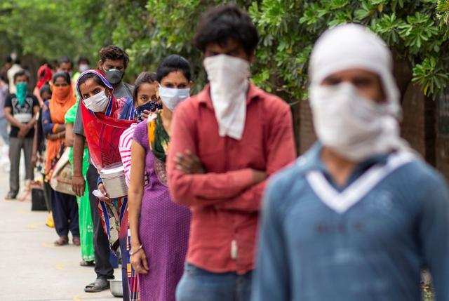 FILE PHOTO: People wait to receive free food at an industrial area, during an extended nationwide lockdown to slow the spreading of the coronavirus disease (COVID-19) in New Delhi, India, April 23, 2020. REUTERS/Danish Siddiqui/File Photo