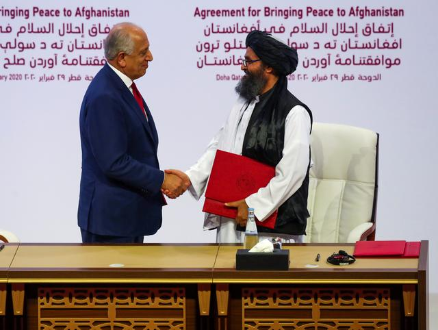 FILE PHOTO: Mullah Abdul Ghani Baradar, the leader of the Taliban delegation, and Zalmay Khalilzad, U.S. envoy for peace in Afghanistan, shake hands after signing an agreement at a ceremony between members of Afghanistan's Taliban and the U.S. in Doha, Qatar February 29, 2020. REUTERS/Ibraheem al Omari/File Photo