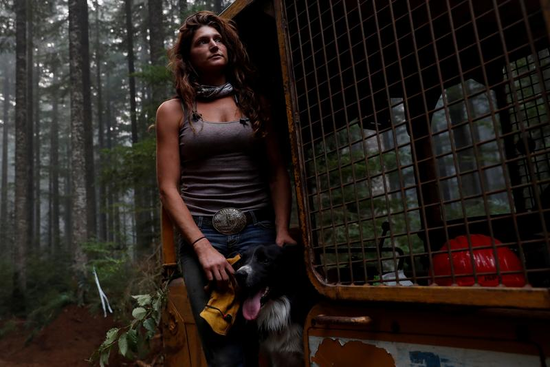 Nicole West, part of the Hillbilly Brigade of some 1,200 men and women who spontaneously came together to fight fires, stands for a portrait petting her dog Oink on a bulldozer during the aftermath of the Riverside Fire near Molalla, Oregon, U.S., September 16, 2020. Picture taken September 16, 2020. REUTERS/Shannon Stapleton